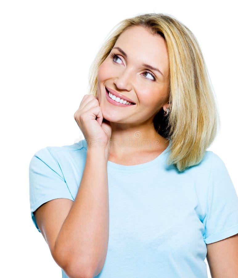 Χαμογελώντας σκεπτόμενη γυναίκα που ανατρέχει στοκ φωτογραφία