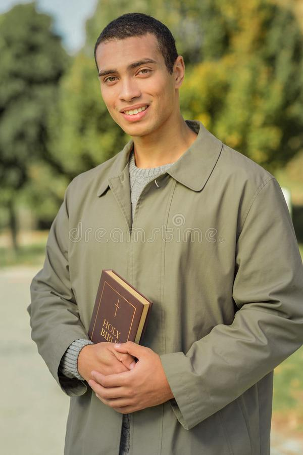 Χαμογελώντας σκοτεινός-μαλλιαρός νεαρός άνδρας που είναι οπαδός στοκ εικόνες