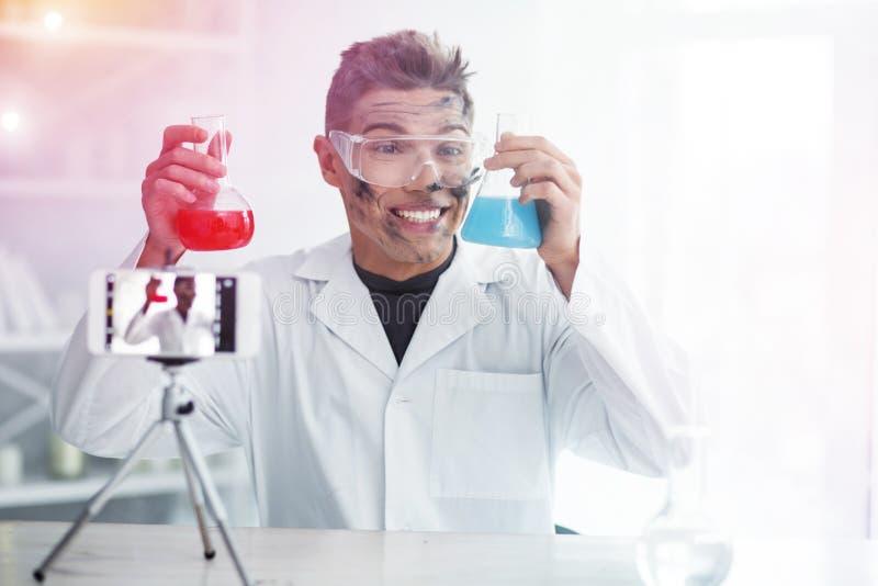 Χαμογελώντας σπουδαστής που αισθάνεται εύθυμος ακόμα και μετά από το ανεπιτυχές πείραμα χημείας στοκ εικόνα