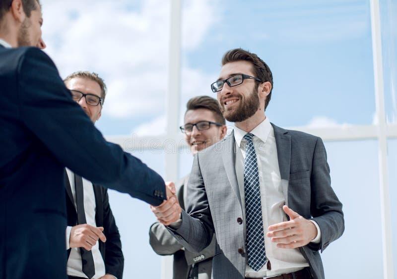 χαμογελώντας συνέταιροι που τινάζουν τα χέρια ο ένας με τον άλλον στοκ εικόνες