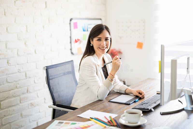 Χαμογελώντας σχεδιαστής στην εργασία στοκ εικόνες