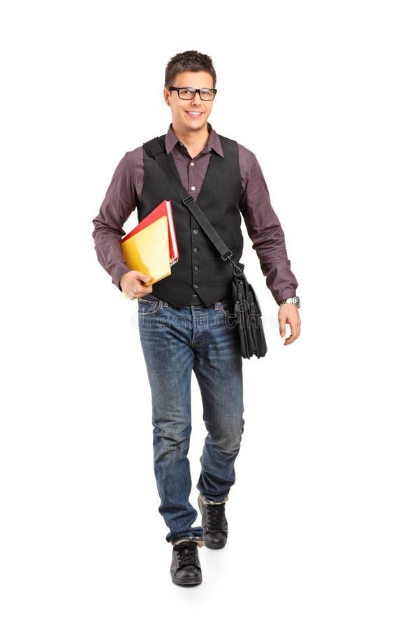 Χαμογελώντας σχολικό αγόρι που περπατά και που κρατά τα βιβλία στοκ φωτογραφίες