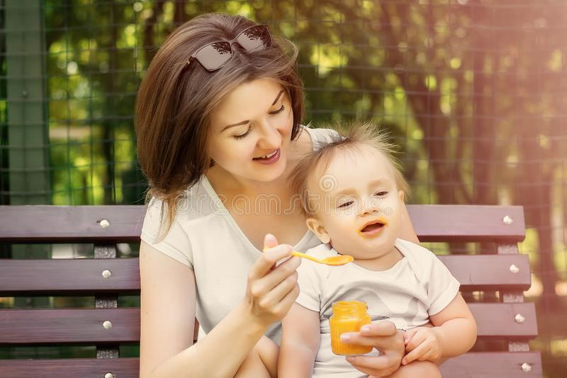 Χαμογελώντας ταΐζοντας παιδί μητέρων με τον πουρέ κολοκύθας στον πάγκο υπαίθριο Το παιδί δεν θέλει να φάει, το μωρό γυρίζει το πρ στοκ φωτογραφία με δικαίωμα ελεύθερης χρήσης