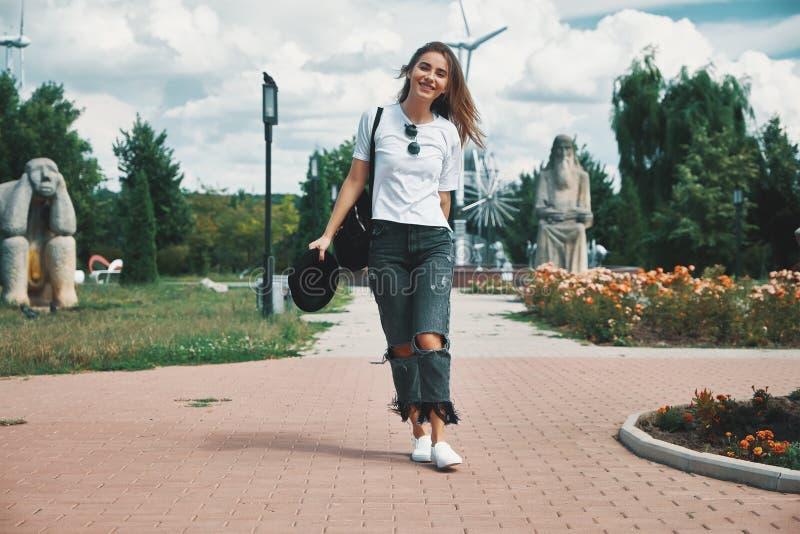 Χαμογελώντας ταξιδιώτης γυναικών με ένα σακίδιο πλάτης σε την πίσω περπάτημα στοκ εικόνες
