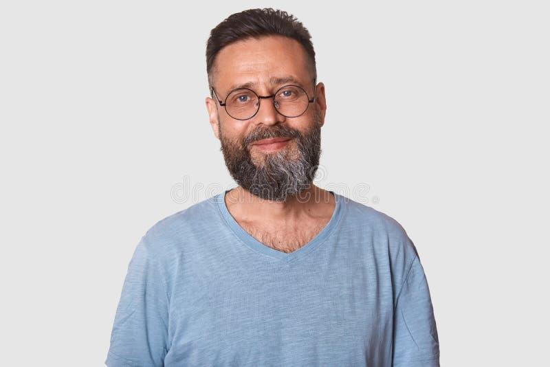 Χαμογελώντας την όμορφη μέση ηλικίας τοποθέτηση ατόμων στο άσπρο κλίμα, φαίνεται εύθυμος Μαύρο μαλλιαρό ελκυστικό πρότυπο με τη φ στοκ φωτογραφία
