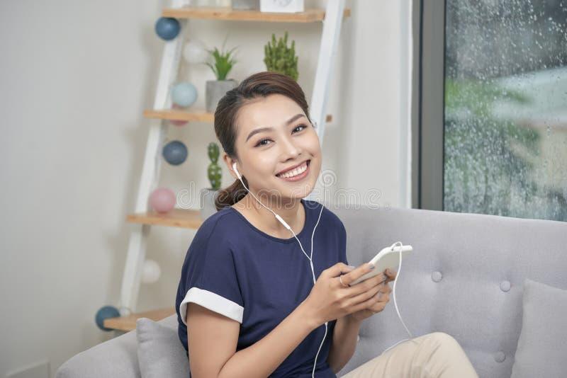 Χαμογελώντας τη χαλάρωση κοριτσιών στο σπίτι, μουσική ακούσματος στα ακουστικά Εσωτερική φωτογραφία της ευτυχούς νέας κυρίας με τ στοκ φωτογραφία
