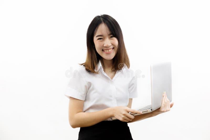 Χαμογελώντας το ευτυχές και εύθυμο ασιατικό θηλυκό επίσημο φόρεμα που κρατά ένα σημειωματάριο lap-top απομονωμένο πέρα από το άσπ στοκ φωτογραφίες