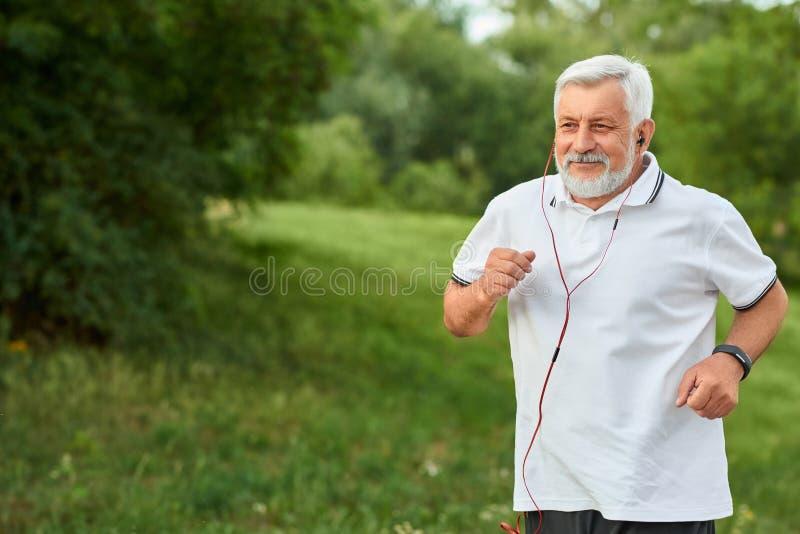Χαμογελώντας τρέχοντας ηληκιωμένος στο πράσινο πάρκο πόλεων στοκ εικόνες
