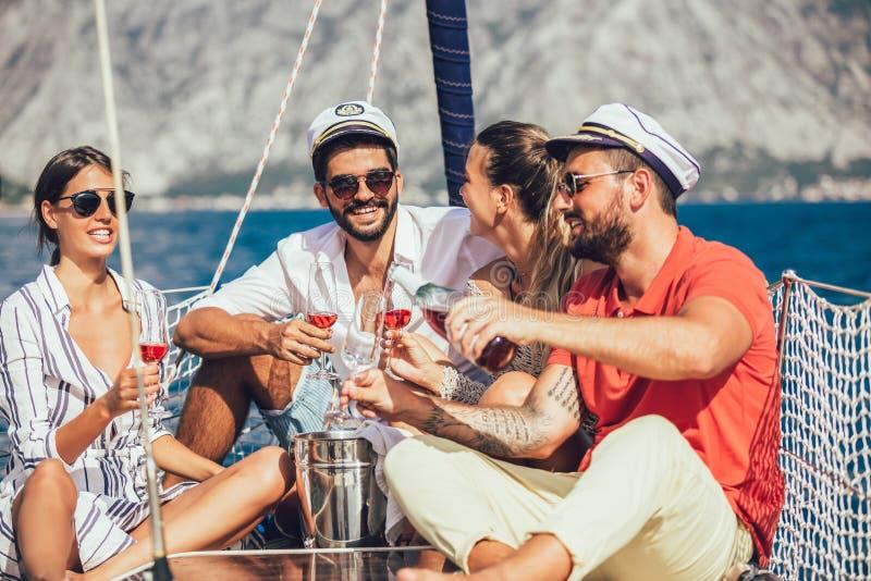 Χαμογελώντας φίλοι που κάθονται sailboat στη γέφυρα και την κατοχή της διασκέδασης στοκ εικόνες με δικαίωμα ελεύθερης χρήσης