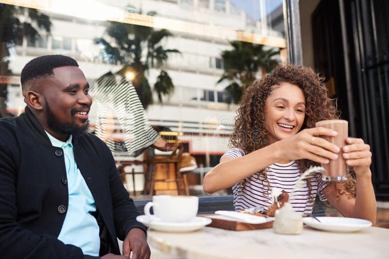 Χαμογελώντας φίλοι που μιλούν μαζί πέρα από τον καφέ σε έναν καφέ πεζοδρομίων στοκ φωτογραφία