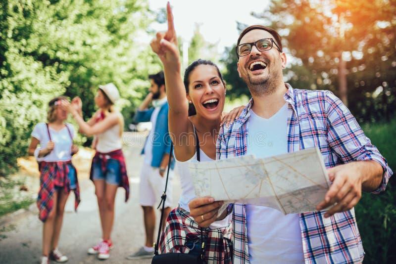 Χαμογελώντας φίλοι που περπατούν με τα σακίδια πλάτης στα ξύλα - περιπέτεια, ταξίδι, τουρισμός, πεζοπορώ και έννοια ανθρώπων στοκ εικόνα με δικαίωμα ελεύθερης χρήσης