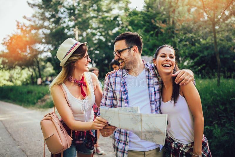 Χαμογελώντας φίλοι που περπατούν με τα σακίδια πλάτης στα ξύλα - περιπέτεια, ταξίδι, τουρισμός, πεζοπορώ και έννοια ανθρώπων στοκ εικόνες με δικαίωμα ελεύθερης χρήσης