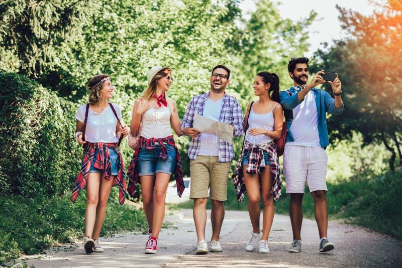 Χαμογελώντας φίλοι που περπατούν με τα σακίδια πλάτης στα ξύλα - περιπέτεια, ταξίδι, τουρισμός, πεζοπορώ και έννοια ανθρώπων στοκ φωτογραφία με δικαίωμα ελεύθερης χρήσης