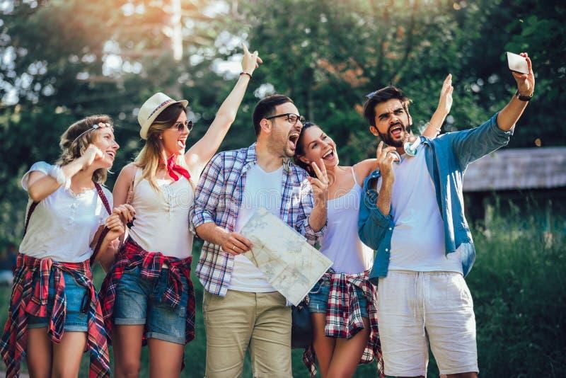 Χαμογελώντας φίλοι που περπατούν με τα σακίδια πλάτης στα ξύλα - περιπέτεια, ταξίδι, τουρισμός, πεζοπορώ και έννοια ανθρώπων στοκ εικόνα
