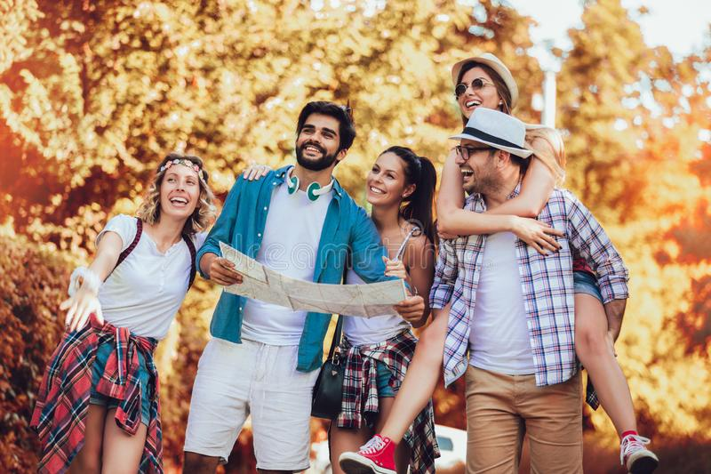 Χαμογελώντας φίλοι που περπατούν με τα σακίδια πλάτης στα ξύλα - περιπέτεια, ταξίδι, τουρισμός, πεζοπορώ και έννοια ανθρώπων στοκ εικόνες