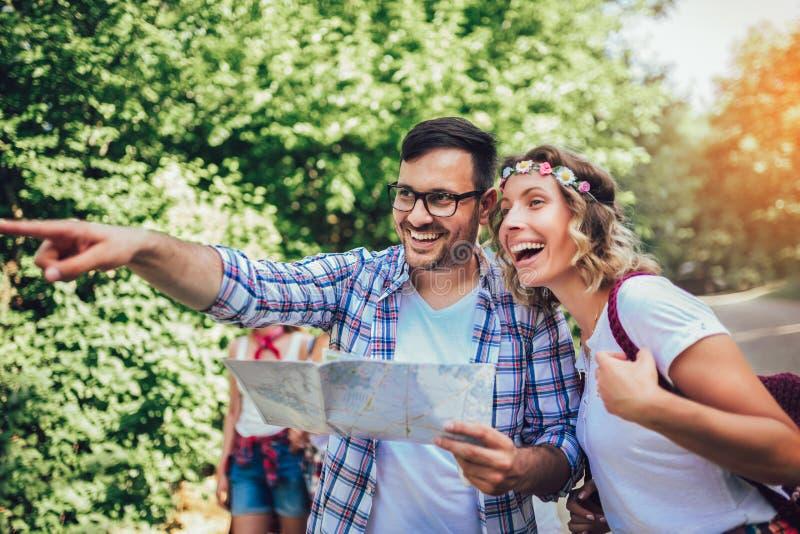 Χαμογελώντας φίλοι που περπατούν με τα σακίδια πλάτης στα ξύλα - περιπέτεια, ταξίδι, τουρισμός, πεζοπορώ και έννοια ανθρώπων στοκ φωτογραφία