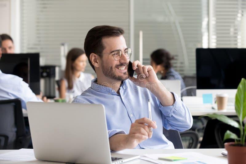 Χαμογελώντας φιλικό άτομο που μιλά στο τηλέφωνο στην αρχή στοκ εικόνα με δικαίωμα ελεύθερης χρήσης