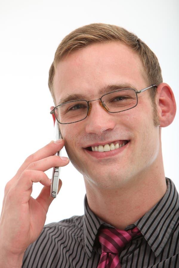 Χαμογελώντας φιλικό άτομο στο κινητό τηλέφωνο στοκ φωτογραφία
