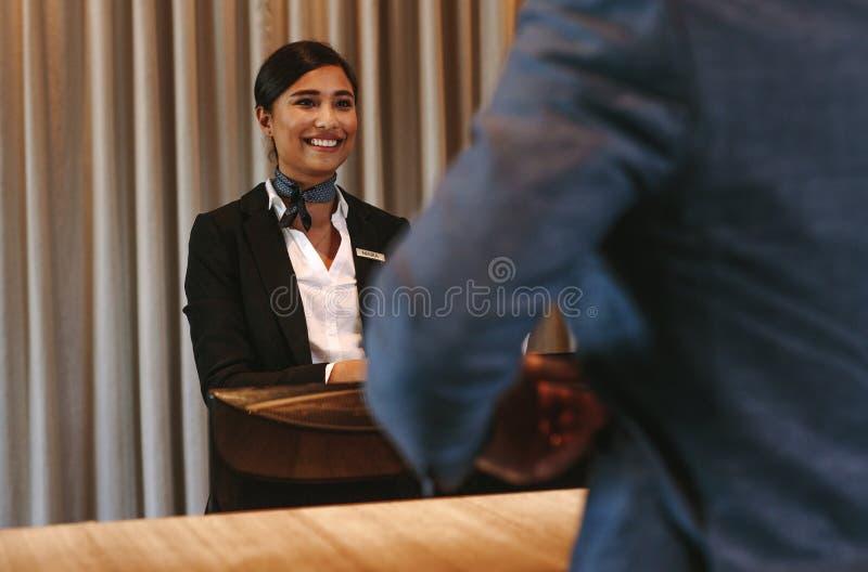 Χαμογελώντας φιλοξενούμενος ρεσεψιονίστ ξενοδοχείων στο μετρητή εισόδου στοκ εικόνες με δικαίωμα ελεύθερης χρήσης