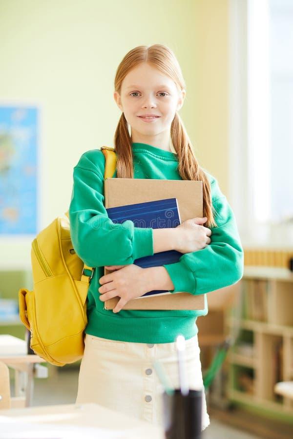 Χαμογελώντας χαριτωμένη μαθήτρια με τα βιβλία στοκ φωτογραφίες