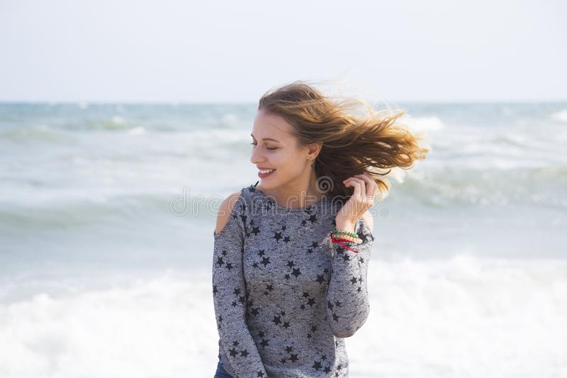 Χαμογελώντας χαριτωμένο νέο ξανθό κορίτσι με την πετώντας τρίχα στην παραλία στοκ φωτογραφίες