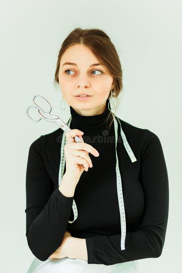 Χαμογελώντας χαριτωμένο seamstress ψαλίδι εκμετάλλευσης και εξέταση τη κάμερα στοκ φωτογραφίες