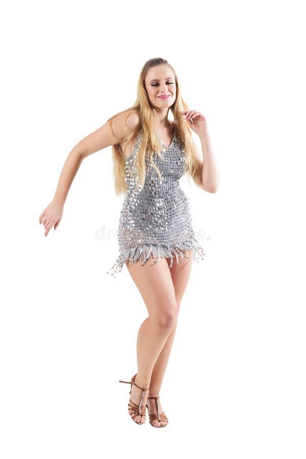 Χαμογελώντας χαρούμενος χορευτής disco γυναικών στο λαμπιρίζοντας λαμπρό ασημένιο φόρεμα στοκ εικόνες