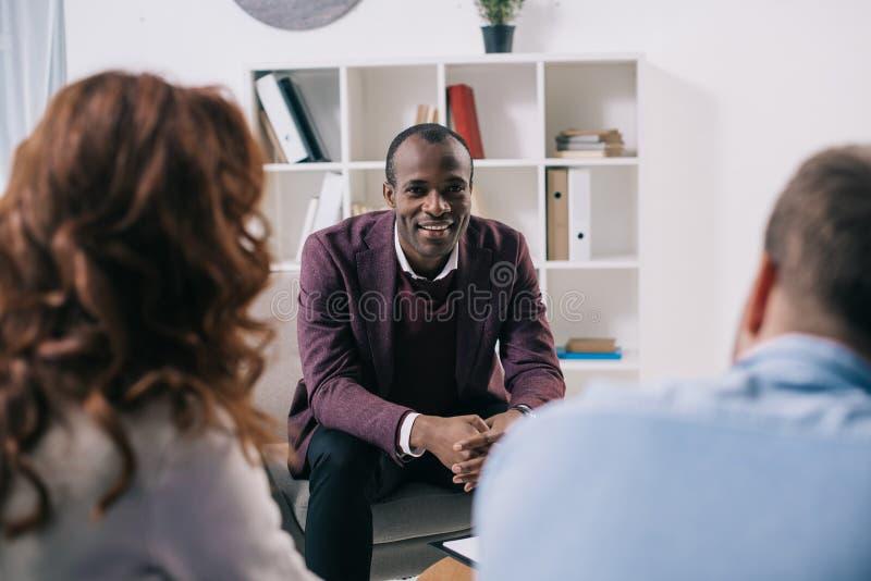 Χαμογελώντας ψυχίατρος που μιλά στη διάζευξη του ζεύγους στοκ εικόνα