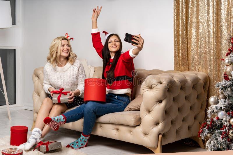 Χαμογελώντας όμορφα νέα κορίτσια στα πουλόβερ και τα καπέλα santa στοκ φωτογραφία