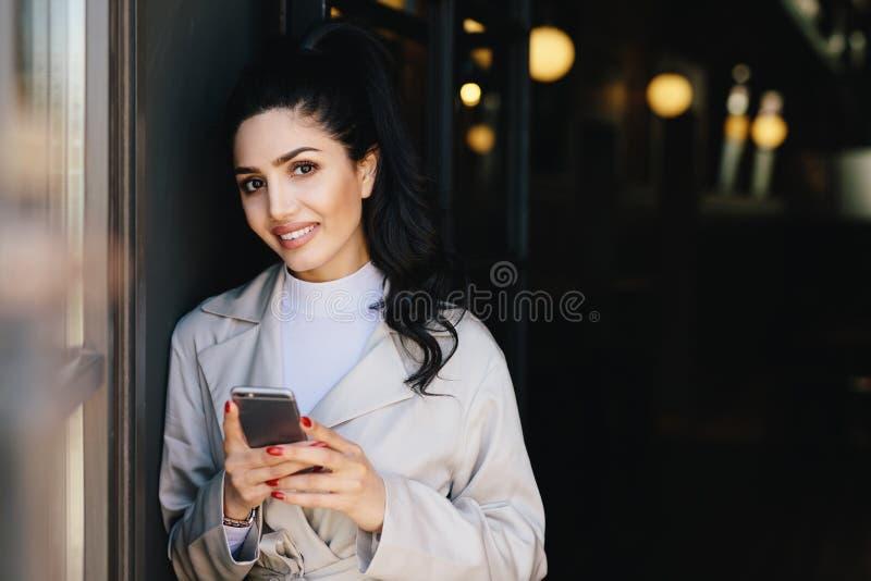 Χαμογελώντας όμορφη γυναίκα brunette με την ουρά πόνι που έχει το κόκκινο μανικιούρ στοκ φωτογραφία με δικαίωμα ελεύθερης χρήσης