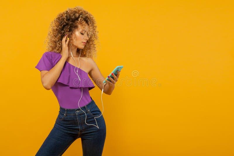Χαμογελώντας όμορφη νέα γυναίκα με τα ακουστικά Κορίτσι με το afro hairstyle και copyspace Κίτρινη ανασκόπηση Έννοια για την πώλη στοκ φωτογραφία με δικαίωμα ελεύθερης χρήσης