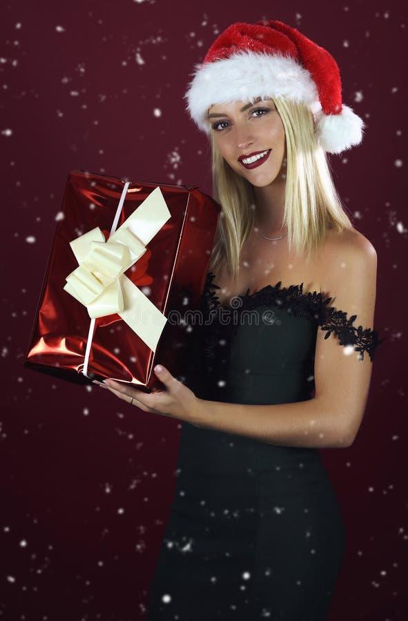 Χαμογελώντας όμορφη ξανθή γυναίκα στο δώρο Χριστουγέννων εκμετάλλευσης καπέλων santa στοκ φωτογραφίες