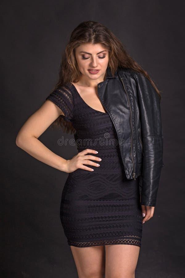 Χαμογελώντας όμορφη σαγηνευτική γυναίκα στο μοντέρνα μαύρα φόρεμα κομμάτων και το σακάκι δέρματος Τα σκοτεινά μάτια smokey αποτελ στοκ εικόνα