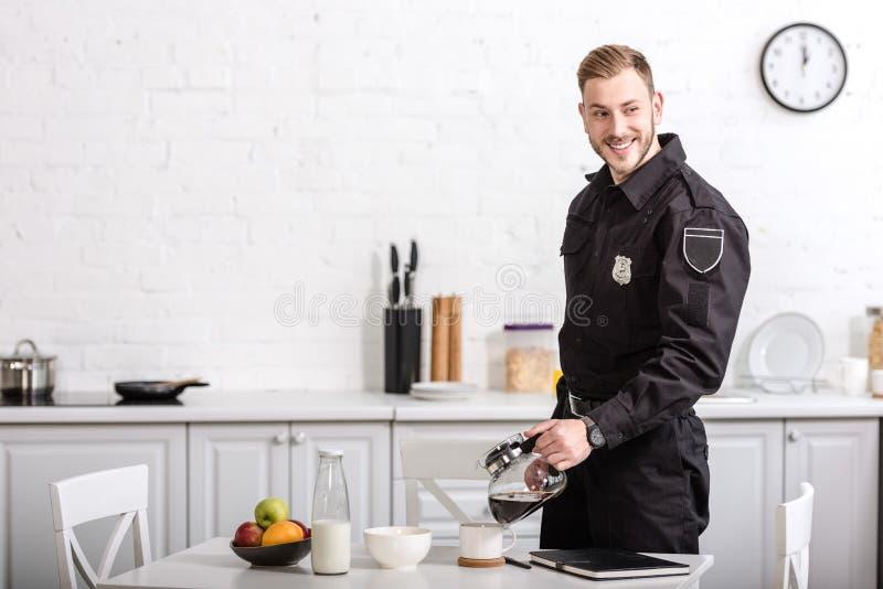 χαμογελώντας όμορφος αστυνομικός που χύνει το φιλτραρισμένο καφέ από το δοχείο γυαλιού στοκ εικόνες