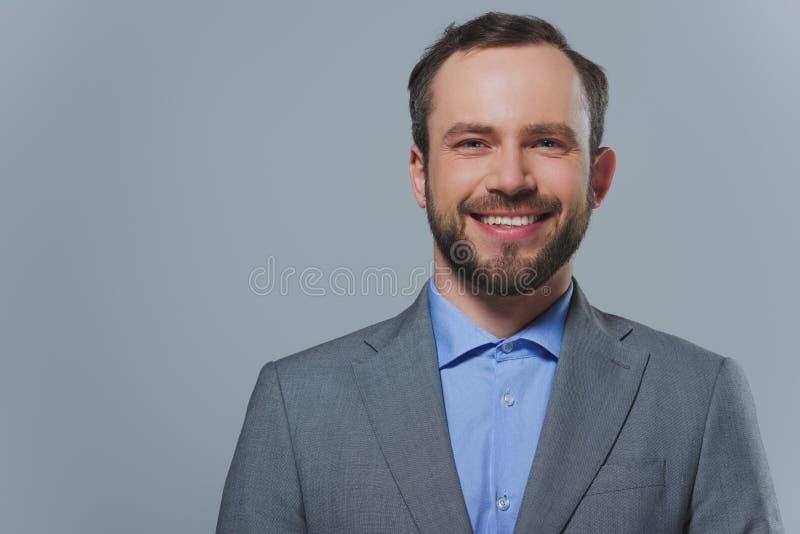 χαμογελώντας όμορφος επιχειρηματίας που εξετάζει τη κάμερα στοκ εικόνες