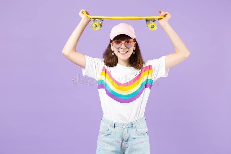Χαμογελώντας όμορφο κορίτσι εφήβων ζωηρά eyeglasses καρδιών ενδυμάτων που κρατά κίτρινο skateboard από πάνω απομονωμένο στην ιώδη στοκ φωτογραφία
