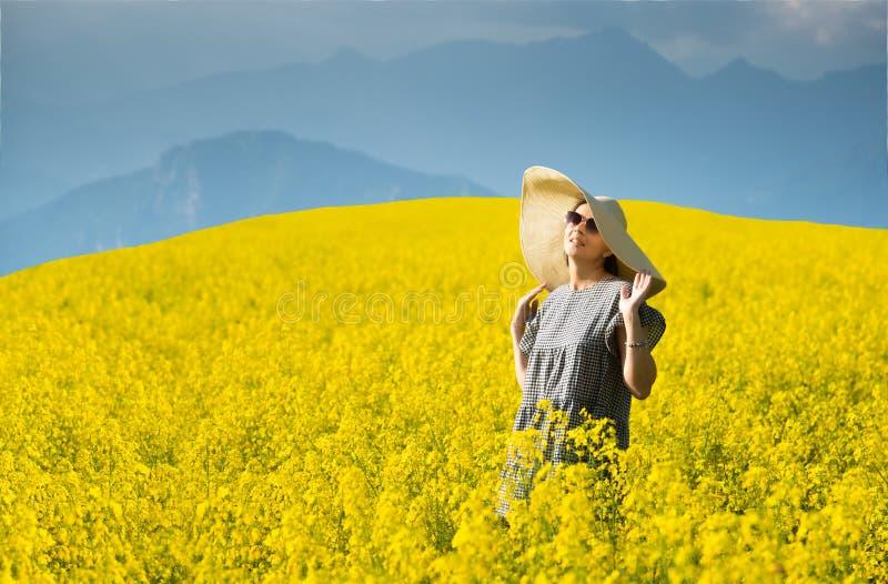 Χαμογελώντας όμορφο κορίτσι στον ανθίζοντας κίτρινο τομέα στοκ εικόνα