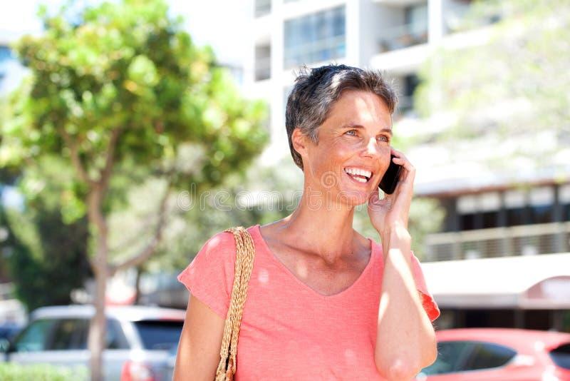 Χαμογελώντας ώριμη γυναίκα που μιλά στο κινητό τηλέφωνο υπαίθρια στοκ φωτογραφίες