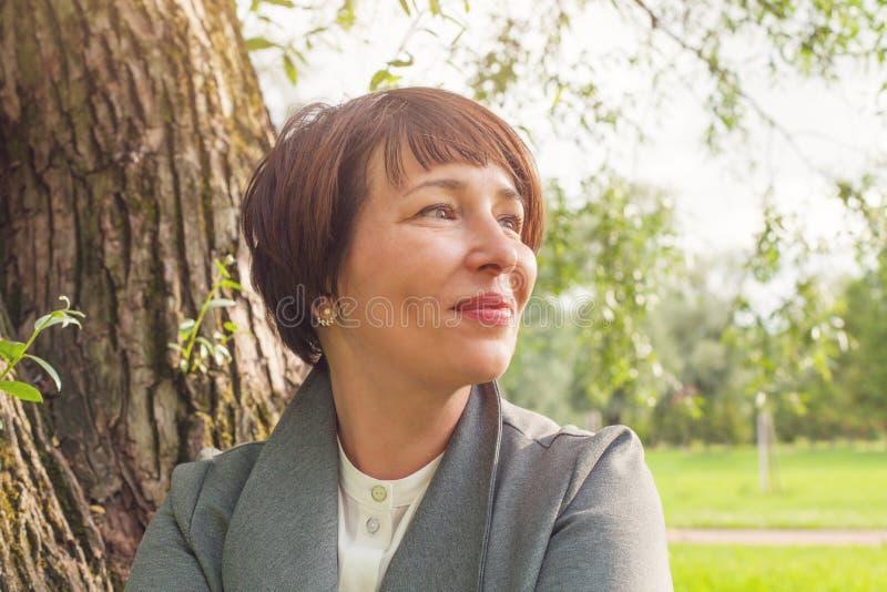 Χαμογελώντας ώριμη γυναίκα που στηρίζεται υπαίθρια, πορτρέτο κινηματογραφήσεων σε πρώτο πλάνο προσώπου στοκ εικόνα