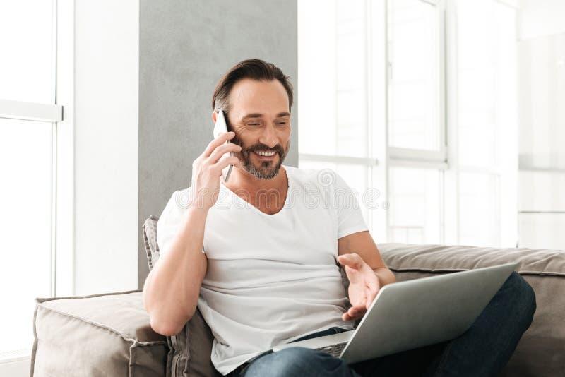 Χαμογελώντας ώριμο άτομο που μιλά στο κινητό τηλέφωνο στοκ φωτογραφία