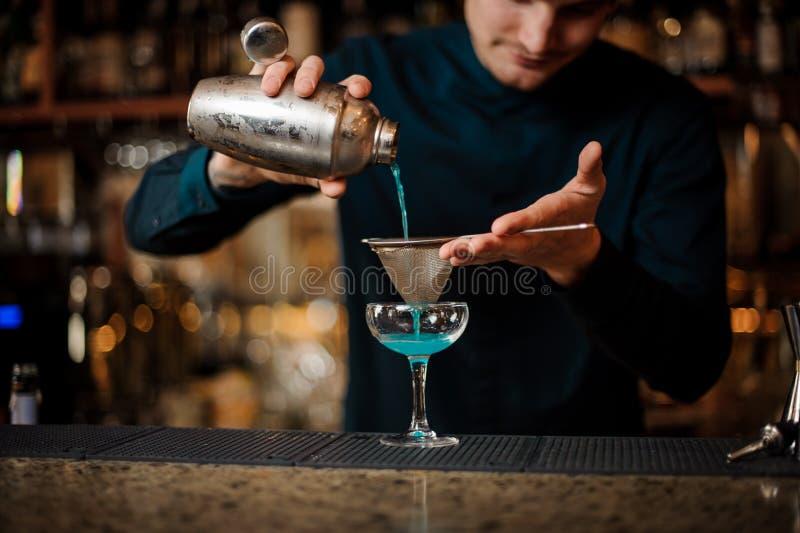 Χαμογελώντας bartender που χύνει το χυμό με το μπλε ποτό από έναν δονητή σε ένα γυαλί που χρησιμοποιεί το διηθητήρα στοκ φωτογραφία με δικαίωμα ελεύθερης χρήσης