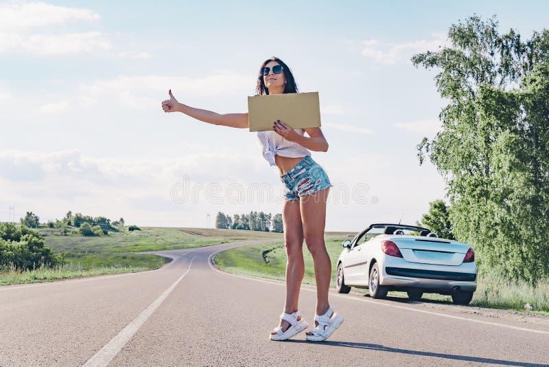 Χαμογελώντας hitchhiker γυναικών στο δρόμο κρατά έναν κενό πίνακα στοκ εικόνα
