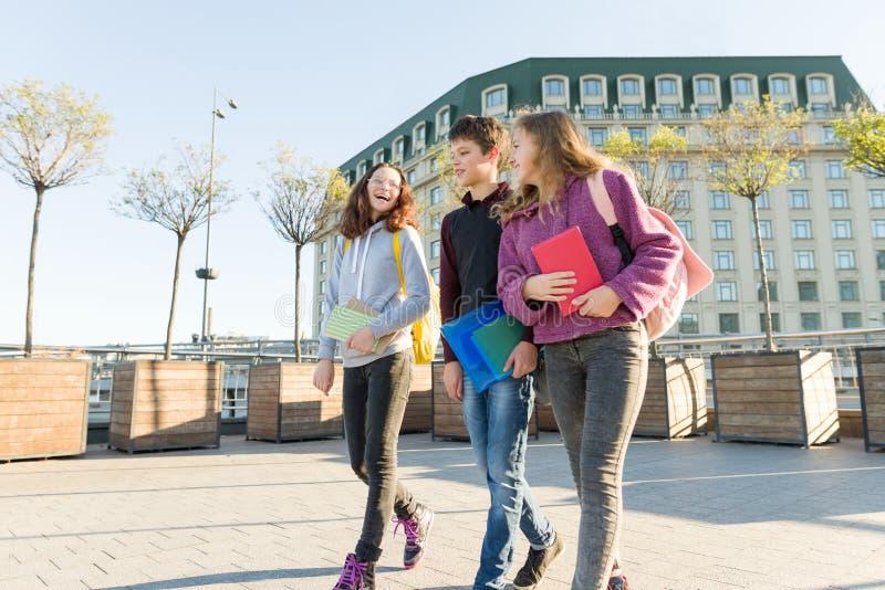 Χαμογελώντας teens σπουδαστές με τα σακίδια πλάτης και τα εγχειρίδια, μιλώντας και πηγαίνοντας προς τα εμπρός στοκ εικόνα
