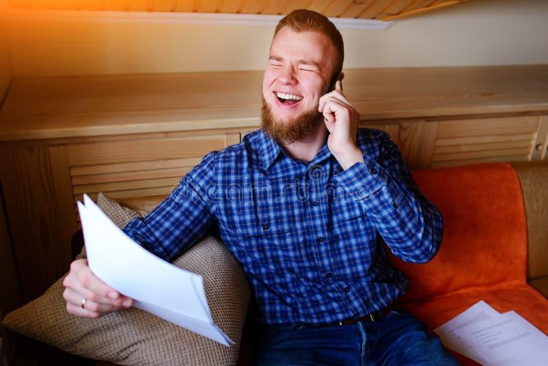 Χαμογελά το ώριμο έγγραφο και την ομιλία εκμετάλλευσης ατόμων στο κινητό τηλέφωνο καθμένος στον καναπέ στο σπίτι στοκ φωτογραφίες με δικαίωμα ελεύθερης χρήσης