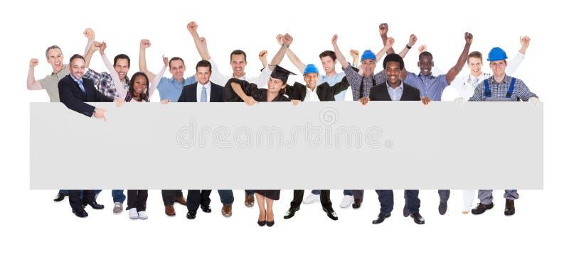 Χαμογελώντας άνθρωποι με τα διάφορα επαγγέλματα που κρατούν τον κενό πίνακα διαφημίσεων στοκ εικόνα με δικαίωμα ελεύθερης χρήσης