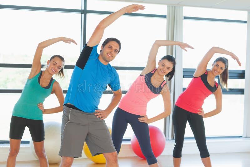 Χαμογελώντας άνθρωποι που κάνουν την άσκηση ικανότητας δύναμης στην κατηγορία γιόγκας στοκ εικόνες