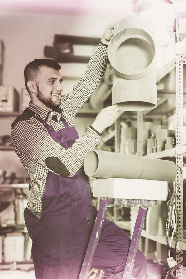 Χαμογελώντας άνδρας εργαζόμενος που επιλέγει τη λεπτομέρεια σωλήνων αγωγών στοκ φωτογραφίες