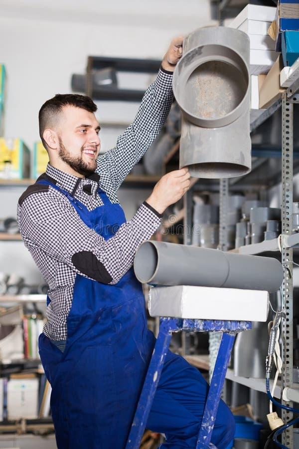 Χαμογελώντας άνδρας εργαζόμενος που επιλέγει τη λεπτομέρεια σωλήνων αγωγών στοκ φωτογραφία με δικαίωμα ελεύθερης χρήσης