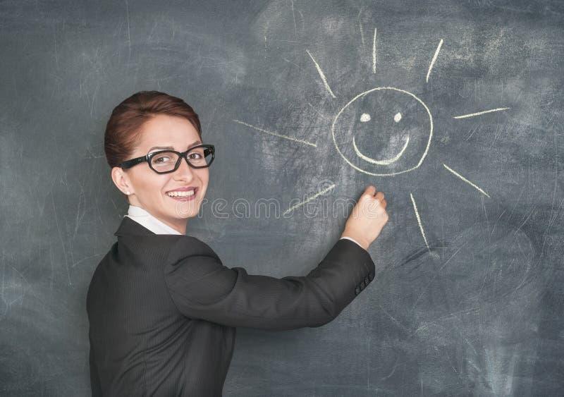 Χαμογελώντας δάσκαλος που χρωματίζει έναν ευτυχή ήλιο στοκ φωτογραφίες με δικαίωμα ελεύθερης χρήσης