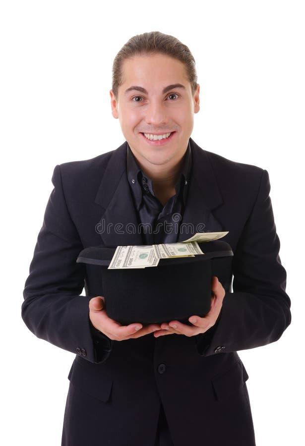 Χαμογελώντας άτομο με τα μετρητά χρημάτων στο καπέλο του στοκ φωτογραφίες